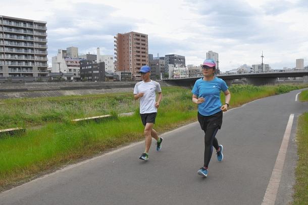 前田編集局長(左)と走る籔下記者=福井市の足羽川沿いで
