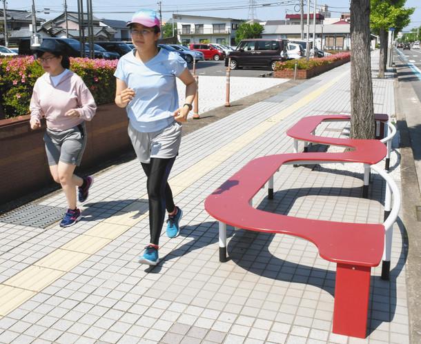 眼鏡のデザインを横目に走る山口記者(左)と籔下記者=鯖江市新横江2で