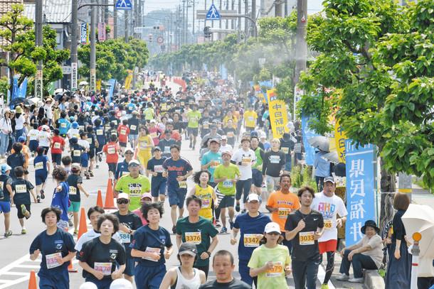 真夏日の奥越路を沿道から噴出されるミストを浴びてゴールを目指す選手たち=大野市糸魚町のこぶし通りで