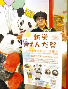 店先のパンダの置物の隣で「新栄ぱんだ祭」をPRする宮田さん 福井市中央1で