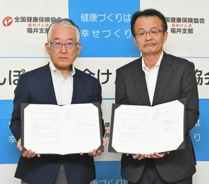 署名した協定書を手にする稲山幹夫会長(左)と畑秀雄支部長⁼福井市の県繊協ビルで