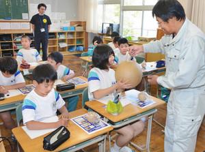 花火玉を持って重さを確かめるなど花火について学んだ児童 越前町四ケ浦小学校で
