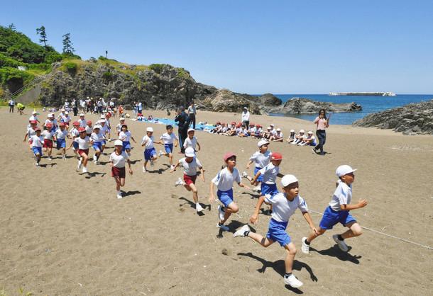 真夏を思わせる青空と海をバックに砂浜を力走する児童たち 30日、福井市の鷹巣海水浴場で
