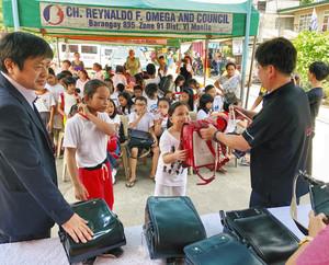 沢崎さん(右)と清水さん(左)からランドセルを受け取る子どもたち フィリピン・マニラ市パンダカン地区で