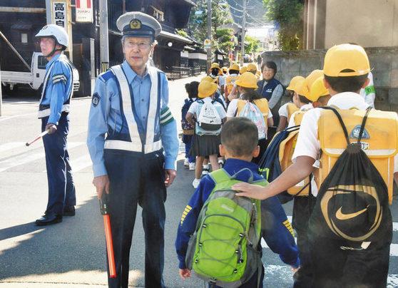 横断歩道を渡る児童を見守る出村さん(手前)や警察官=永平寺町松岡春日1で