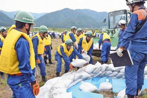 月の輪工法の土のう積み訓練に励む消防団員ら=永平寺町の中島河川公園で