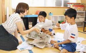 新聞を活用した国語の授業で、ふれあい学級の岩佐有紀教諭(左)から教わる5年の安井祐皓君(中)と1年の松山公歩君 越前町糸生小学校で