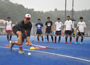 カナダ代表選手(手前)から指導を受ける高校生たち=越前町の県立ホッケー場で