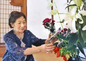 床の間の生け花に手をやる姉崎素心さん=福井市の養浩館庭園で