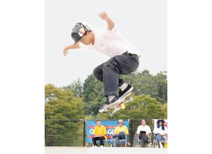 スケートボードの全日本アマ選手権出場を懸けて演技する選手と、審判を務める上杉政充さん(左下)=福井市のふくい健康の森スケートパークで
