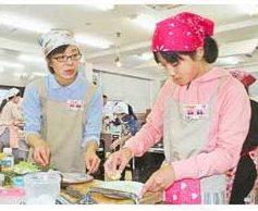 真剣な表情で調理する優秀賞の永井美穂さん(左)、希実さん親子