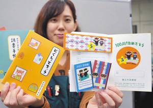 読書手帳(左)の5周年記念キャンペーンで配布されるしおりやシール、豆ノート=鯖江市図書館で