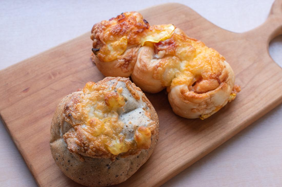 手前)ゴマの風味が際立つ「すりごまチーズパン」 後ろ)ズッキーニの食感がアクセント「ズッキーニベーコンピザパン」